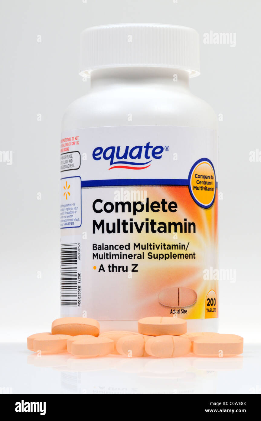 Bottle of Equate Multivitamins with tabs scattered on white background, cutout - Stock Image