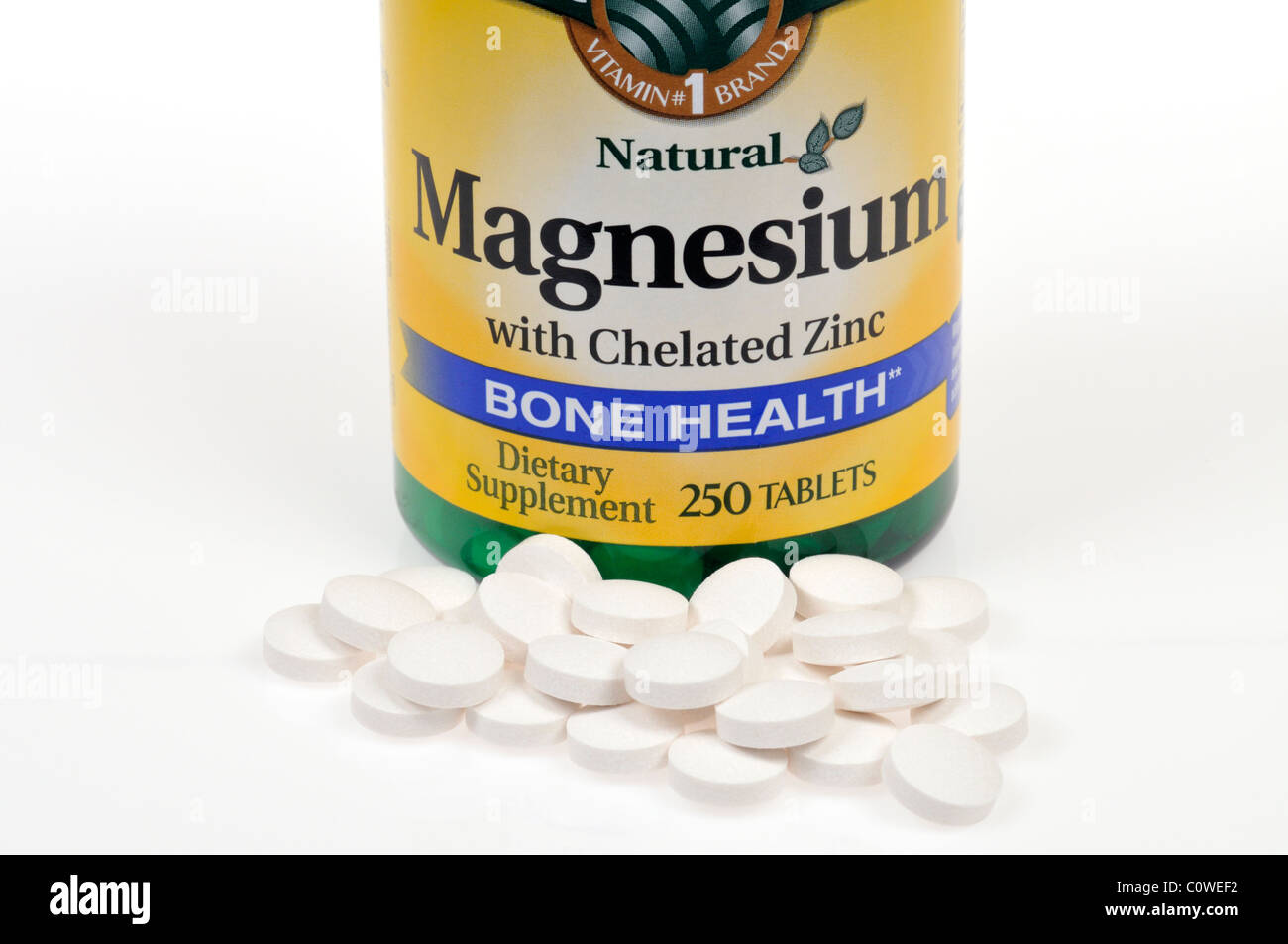 Bottle of Magnesium dietary supplement with tablets scattered on white background. Stock Photo