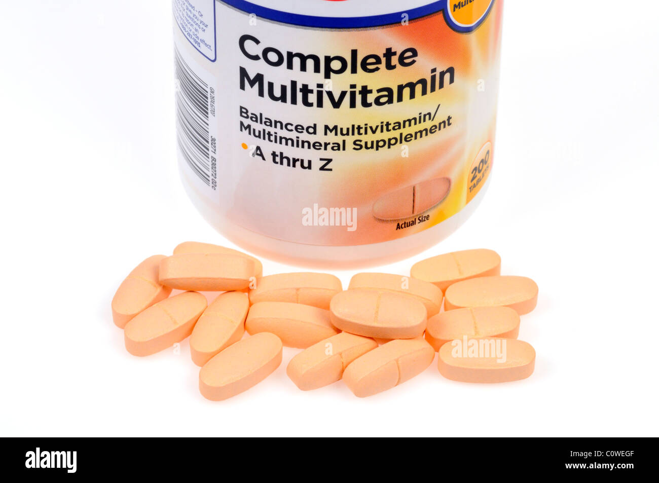 Bottle of Multivitamins with tabs scattered on white background - Stock Image