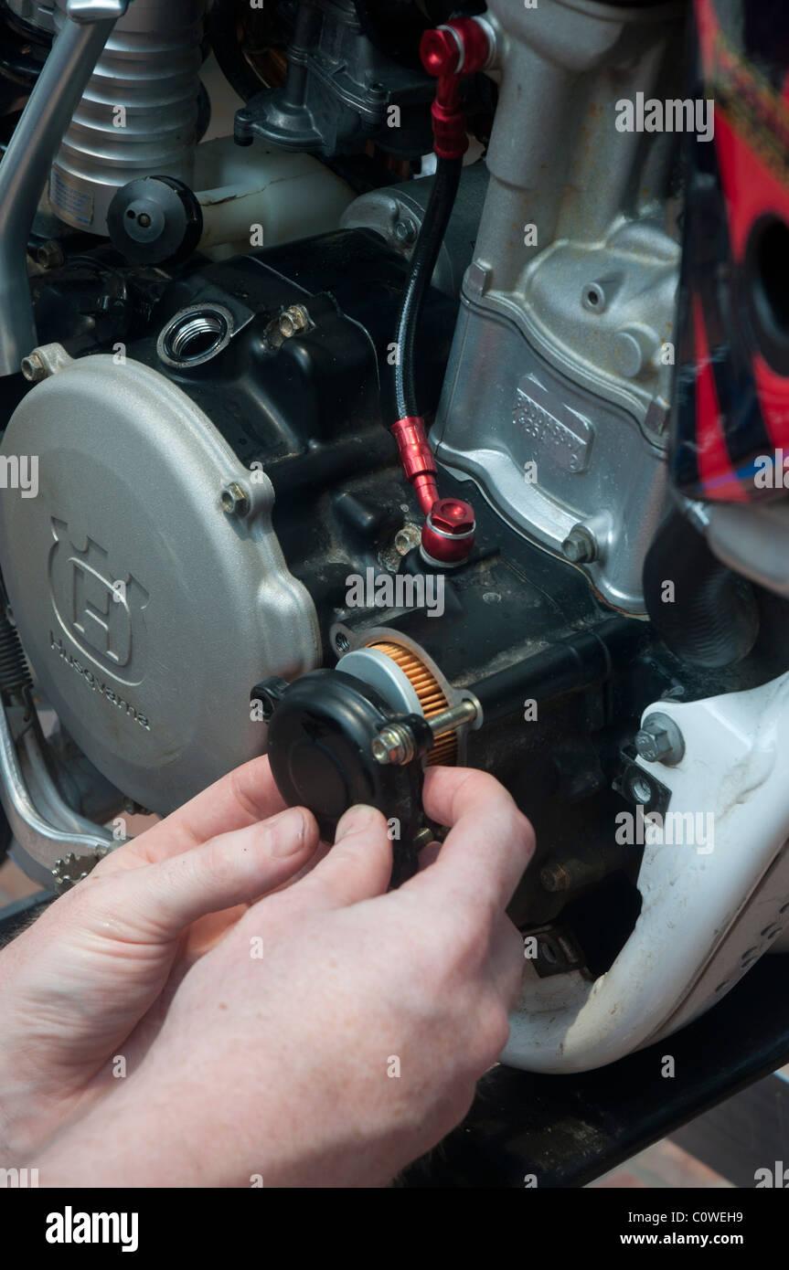 Replacing oil filter in Husqvarna motor cross bike - Stock Image