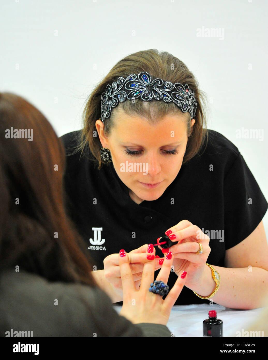 Beautician applying nail varnish at Excel - Stock Image