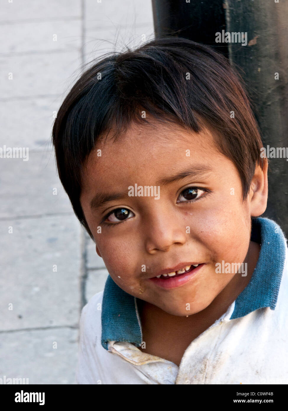 small winsome Mexican indigenous boy with soulful brown eyes & bad teeth looks hopefully at the camera Oaxaca - Stock Image