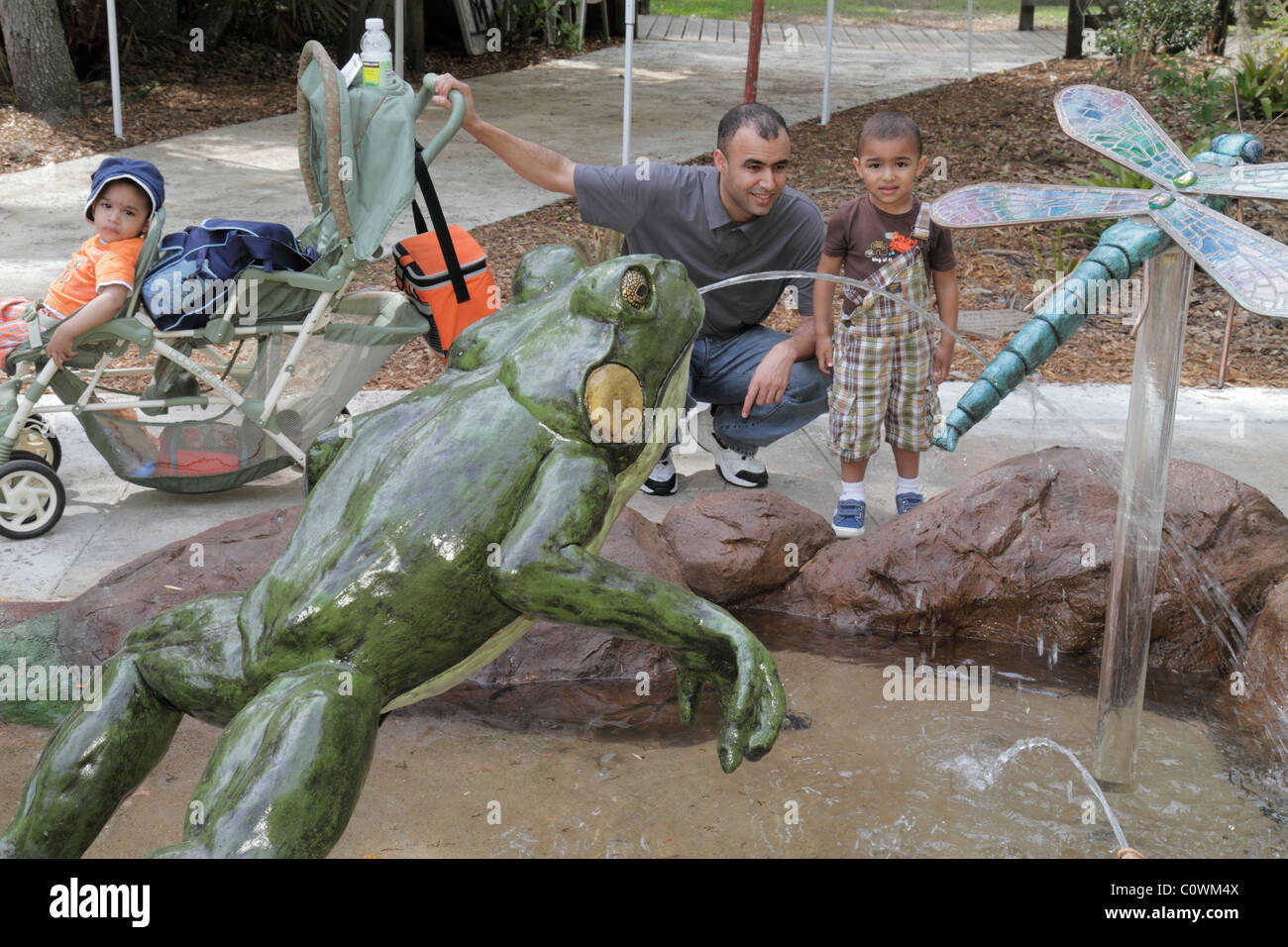 Orlando Florida Sanford Central Florida Zoo & and Botanical Gardens Middle Eastern man boy son family water - Stock Image