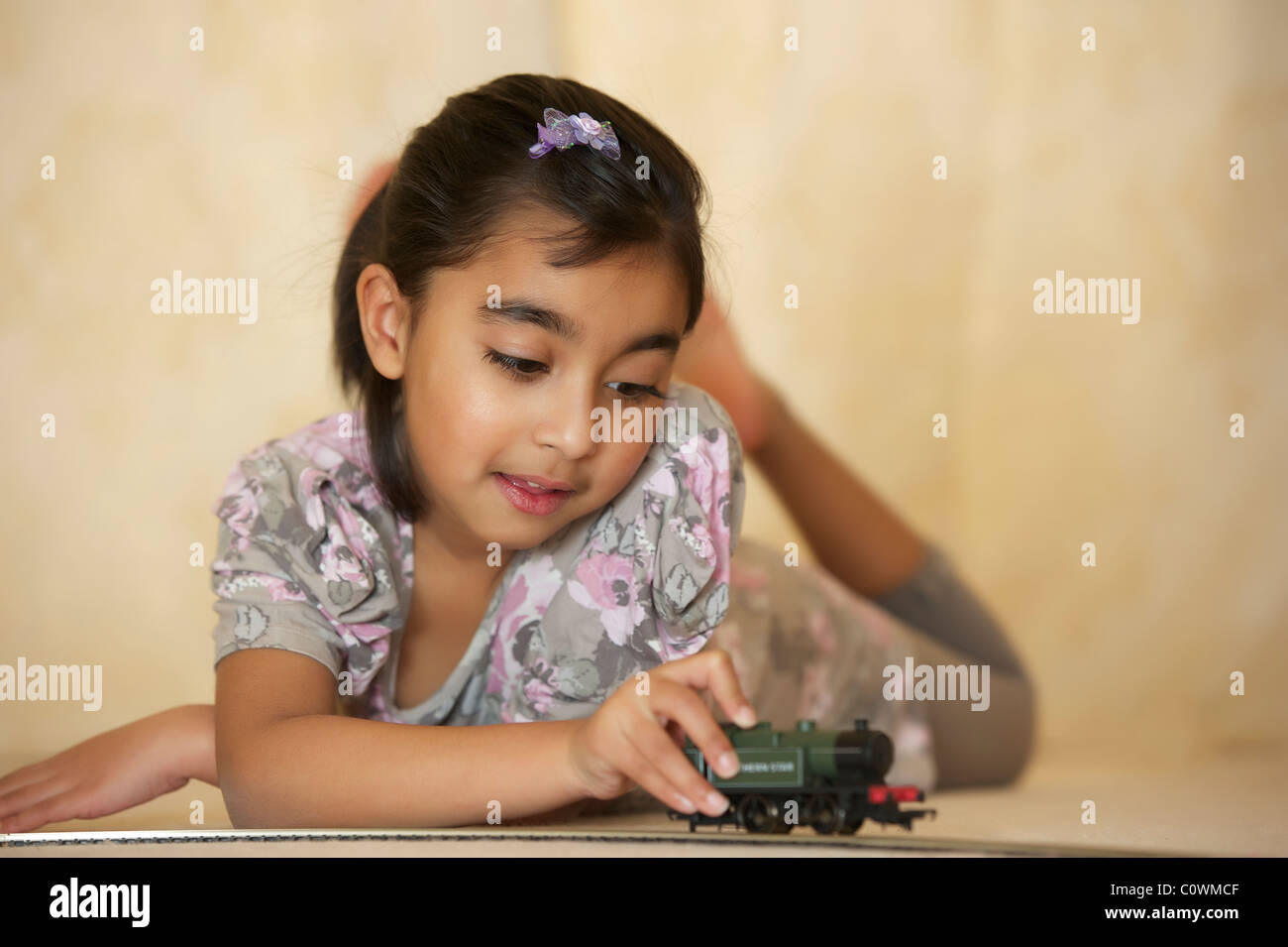 A young girl playing with her toy train set Stock Photo