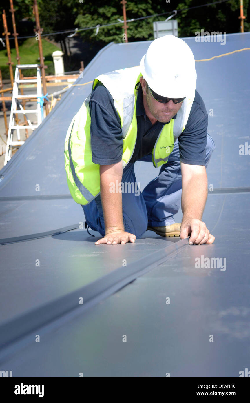 Construction workers working on office building roof, Edinburgh Scotland UK - Stock Image