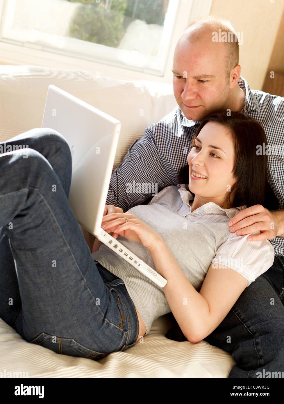 Couple browsing web using laptop - Stock Image
