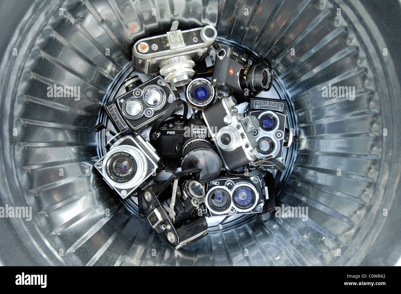 A dustbin of old pre-digital cameras including a Rolliflex, a Hasselblad a Leica and a Nikon - Stock Image
