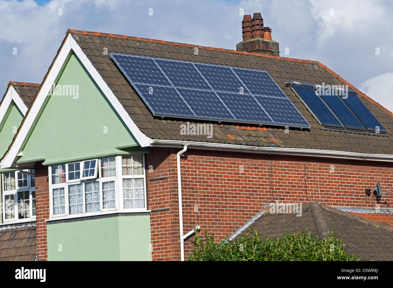 Solar panels for electricity and hot water fitted to roof of residential property in the UK. - Stock Image