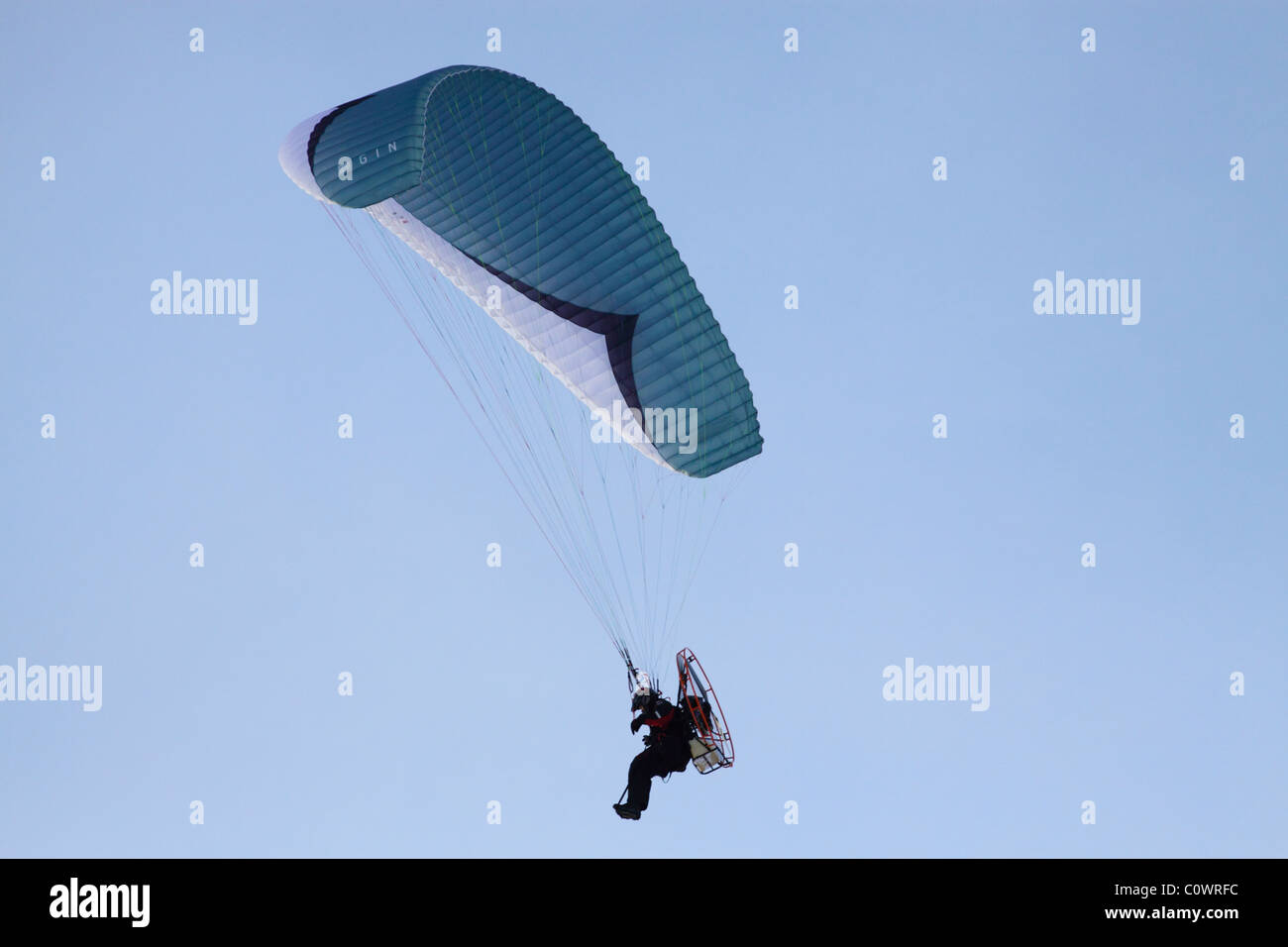 Flying Man - motorized paraglider flying on a clear day - Stock Image