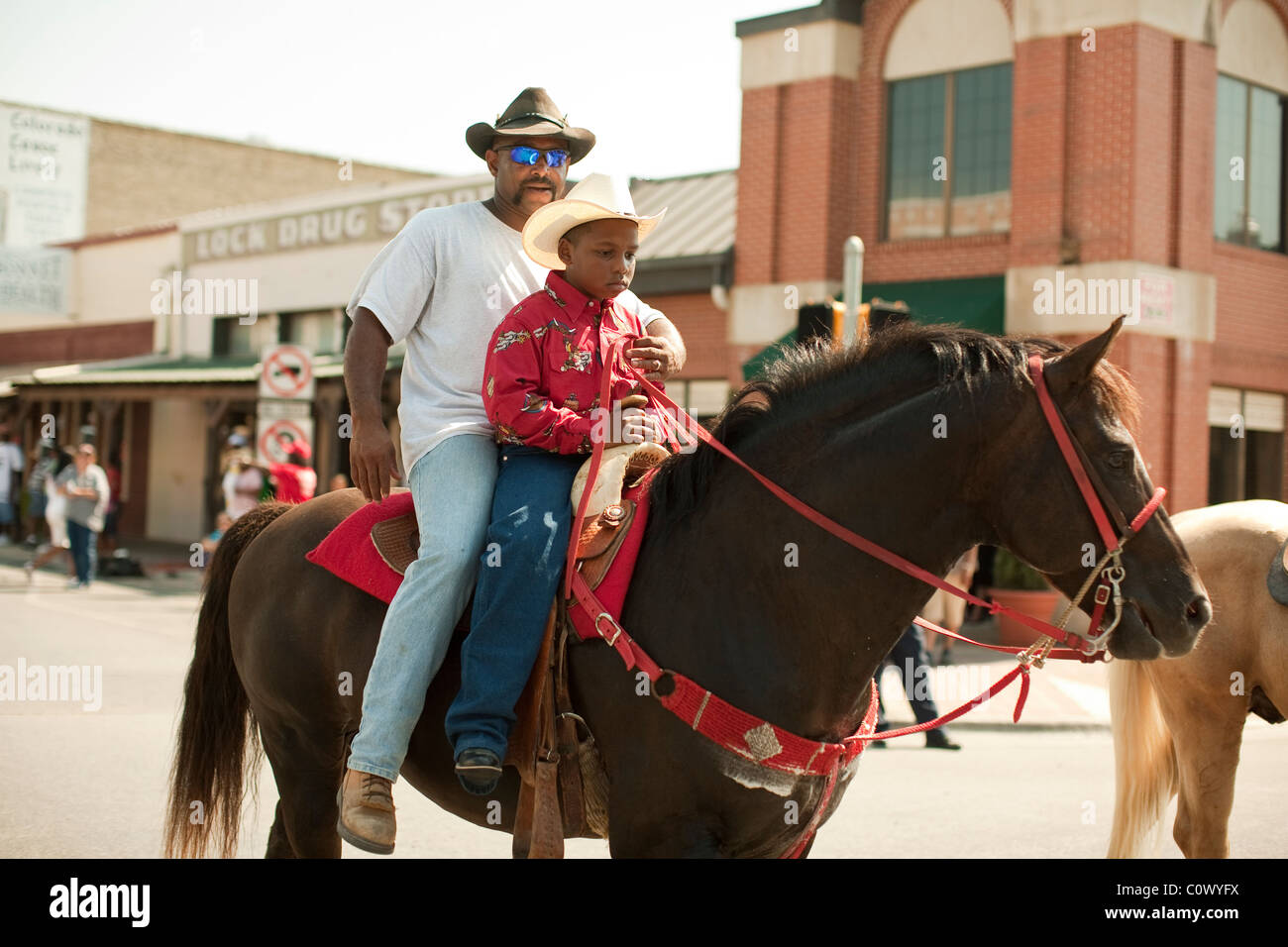 African-American man and boy ride a horse during a parade celebrating Juneteenth in downtown Bastrop, Texas - Stock Image