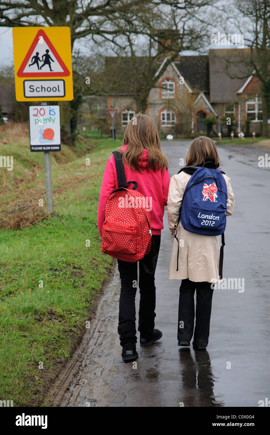 Schoolchildren walking to school along a country lane without pavement or walkway Hampshire England UK - Stock Image