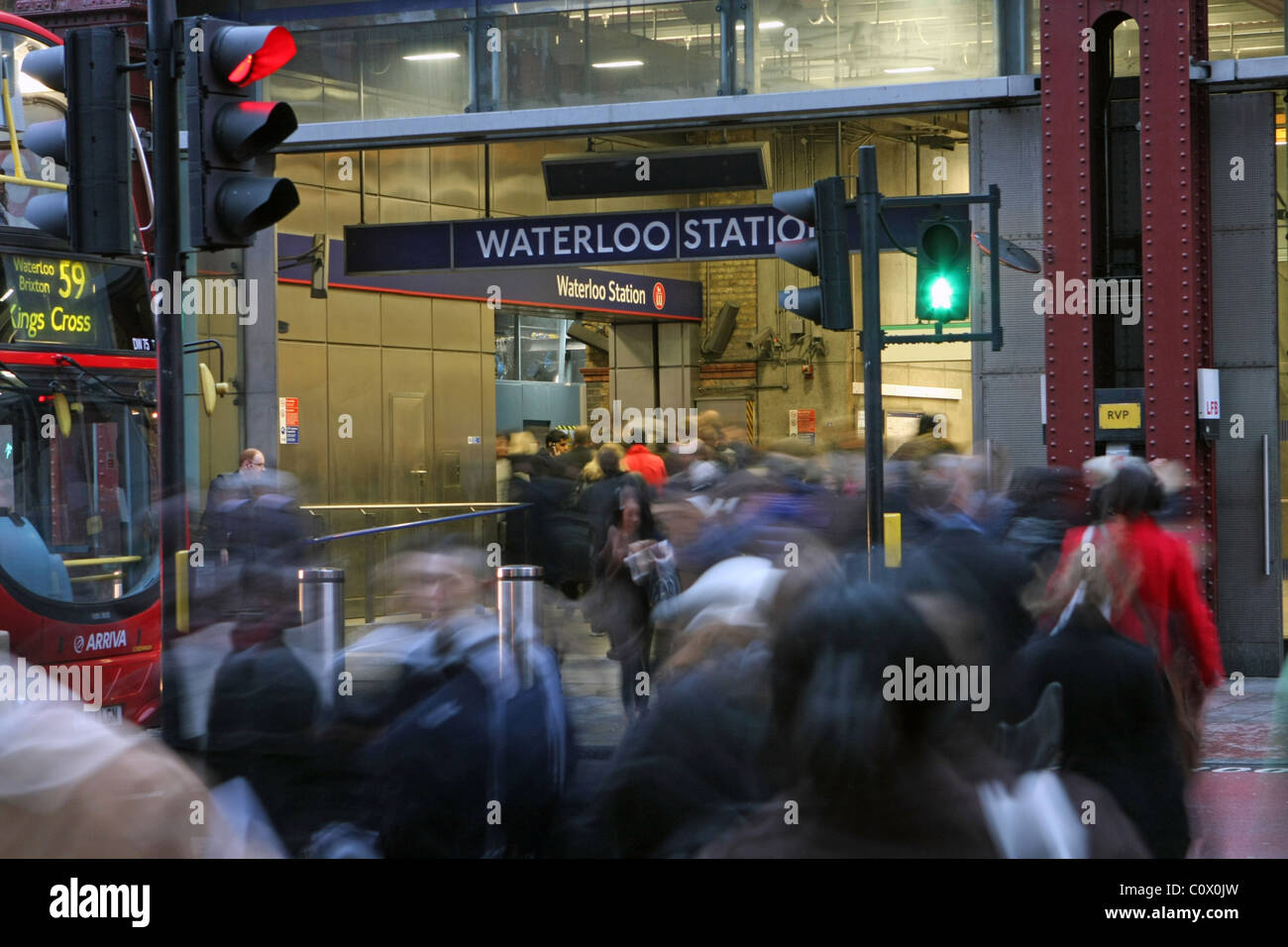 People crossing the road and walking into Waterloo train station in the evening rush hour, a bus and traffic lights - Stock Image