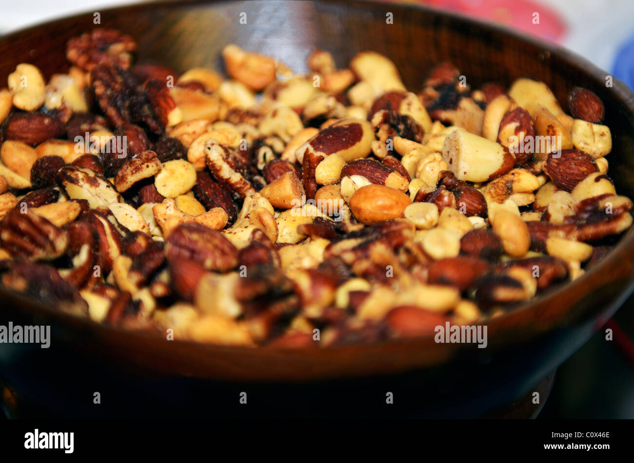 A wooden bowl filled with roasted, salted mixed nuts. Closeup. - Stock Image