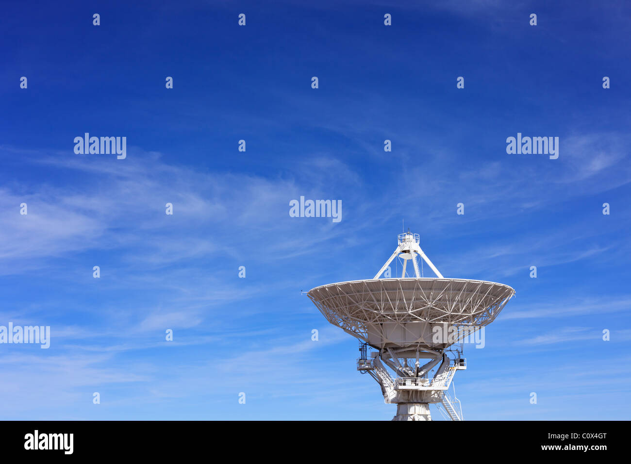 A radio telescope dish in the Very Large Array against blue New Mexico sky. Stock Photo