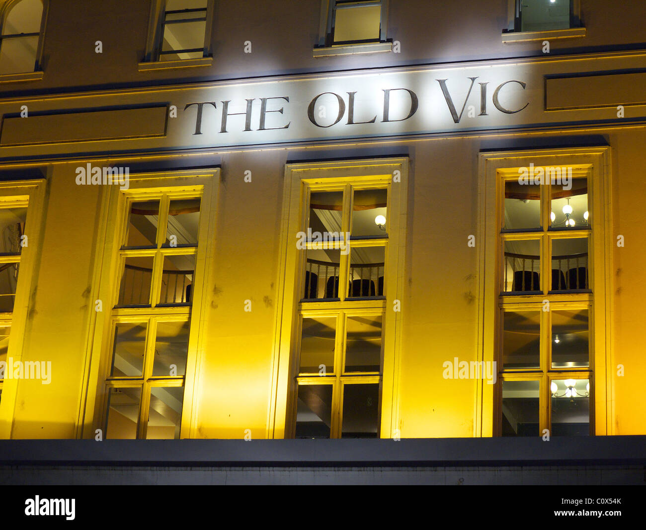 Close-up front view of The Old Vic theatre floodlit at night in London - Stock Image