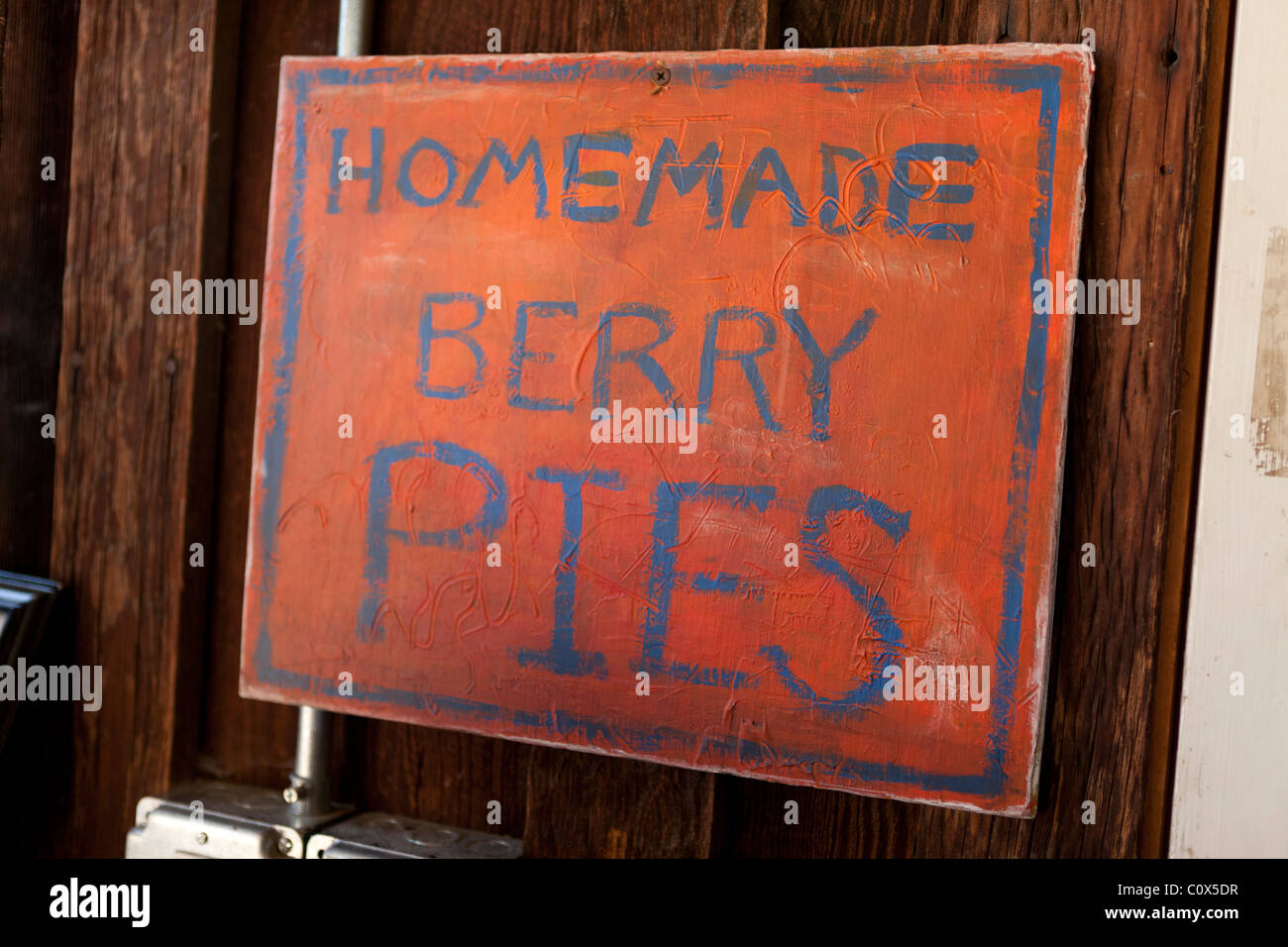 Hand-painted sign reading 'Homemade Berry Pies' on wooden wall. Applegate Valley, Oregon.  Pennington Farms. - Stock Image