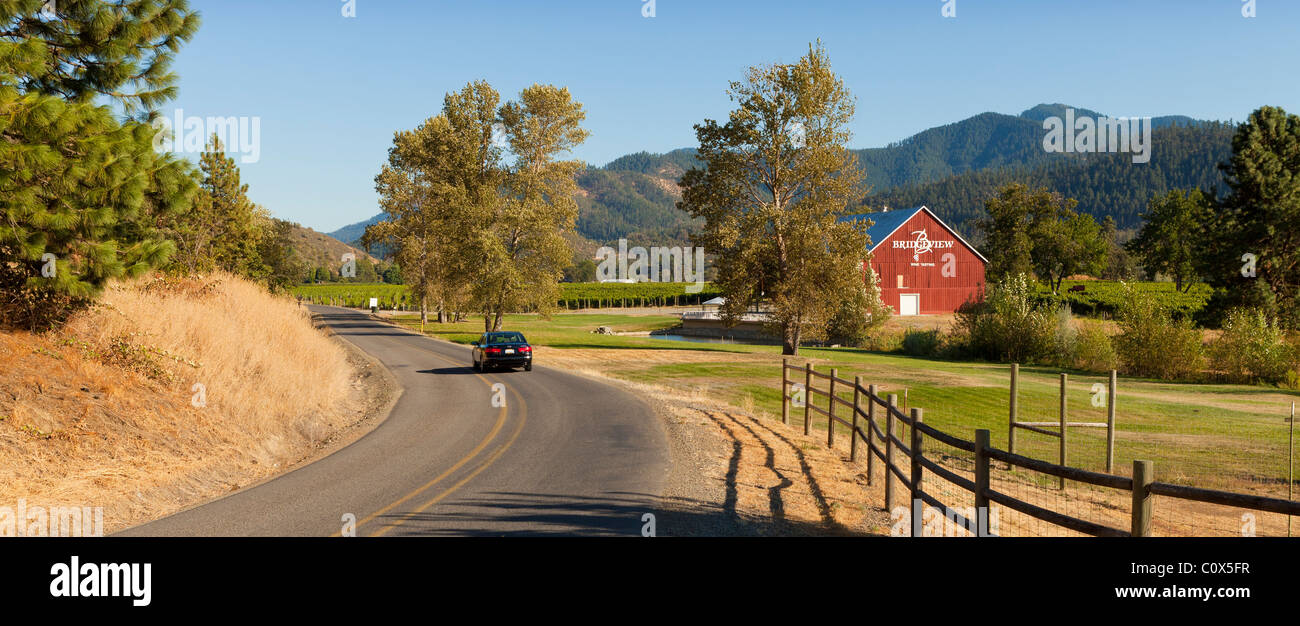 Car driving on North Applegate Road in Applegate Valley, OR past farms, barn, winery. - Stock Image