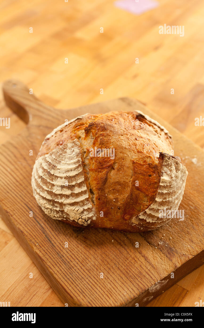 Applegate Valley Artisan Breads; Roasted Garlic & Cheddar Bread. Loaf of bread on bread board on butcher block - Stock Image