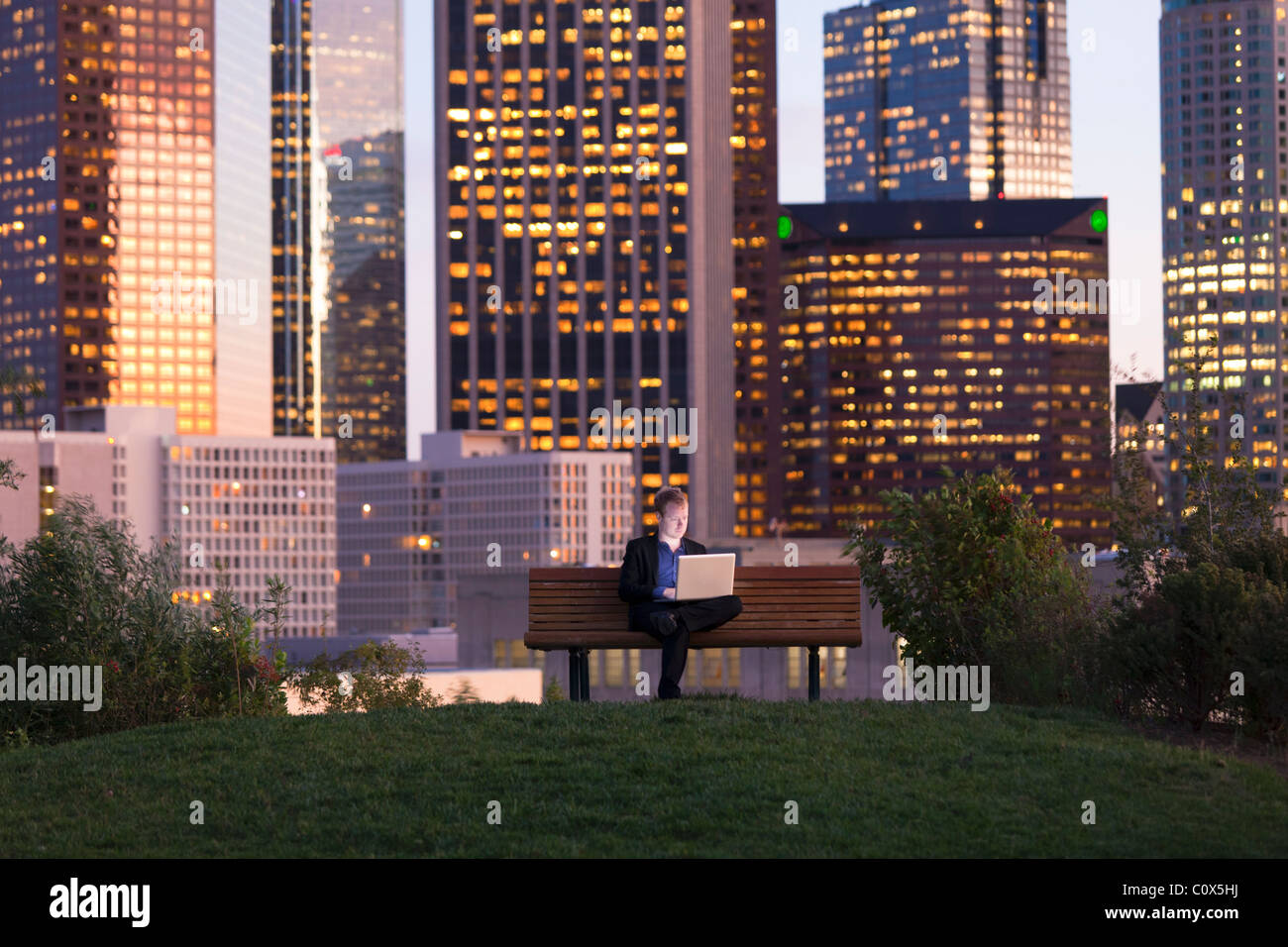 Male sitting on park bench working on laptop computer with Los Angeles city skyline in background at dusk, sunset - Stock Image