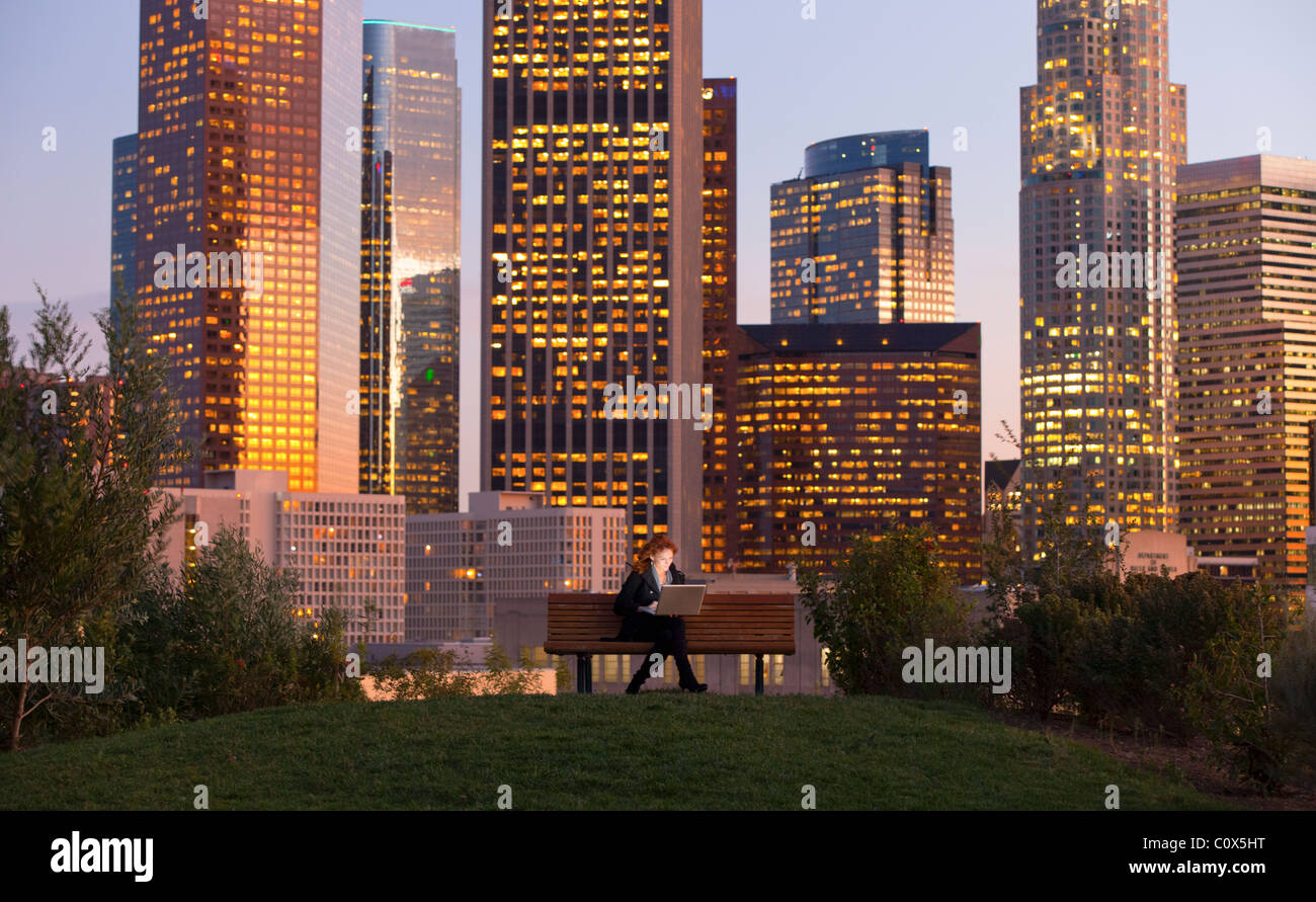 Female sitting on park bench working on laptop computer with Los Angeles city skyline in background at dusk, sunset - Stock Image