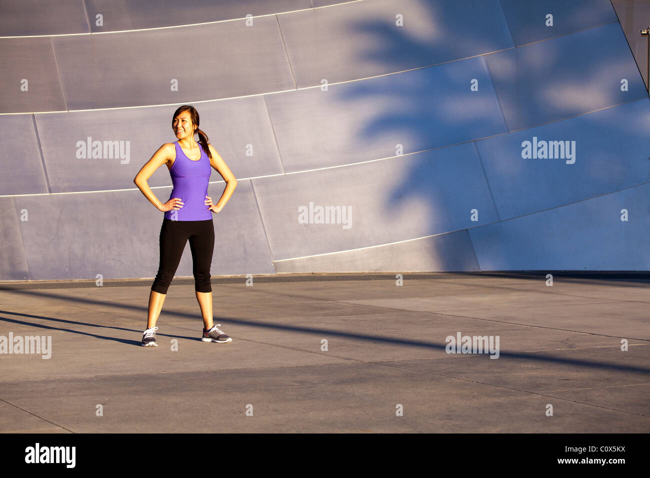 Asian American female runner resting standing in front of metal clad wall.  Purple tank top and black pants. - Stock Image