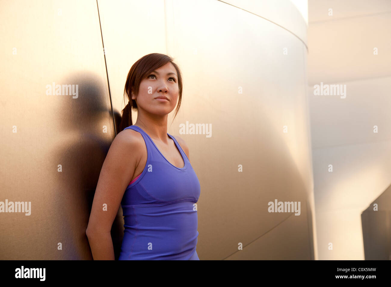 Asian American female runner resting leaning against metal clad wall.  Purple tank top and black pants. - Stock Image