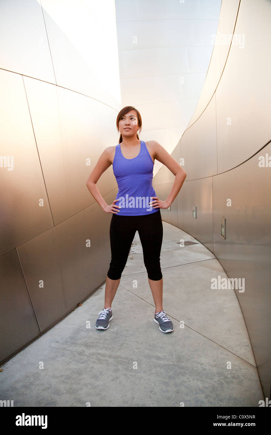 Asian American female runner resting with hands on hips standing in front of metal clad wall.  Purple tank top and - Stock Image