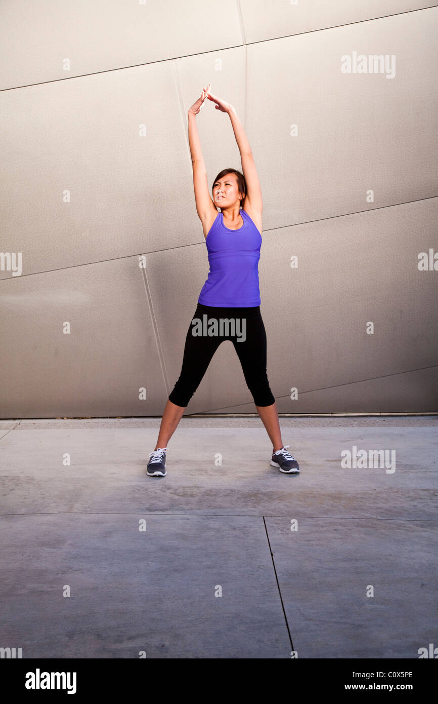 Asian American female runner stretching arms standing in front of metal clad wall.  Purple tank top and black pants. - Stock Image
