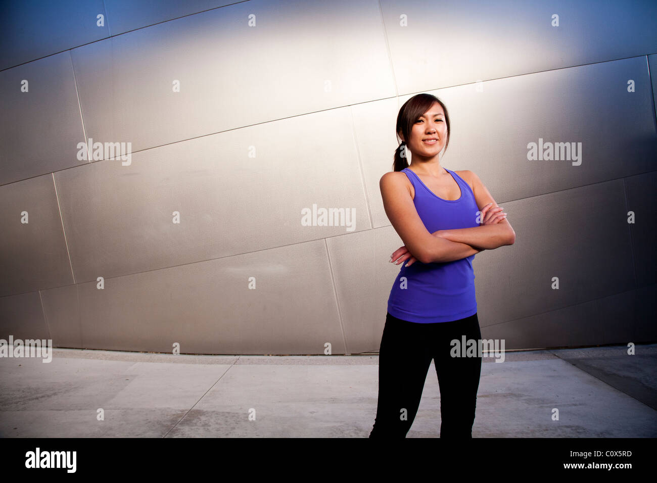 Asian American female runner resting with arms folded standing in front of metal clad wall.  Purple tank top and - Stock Image