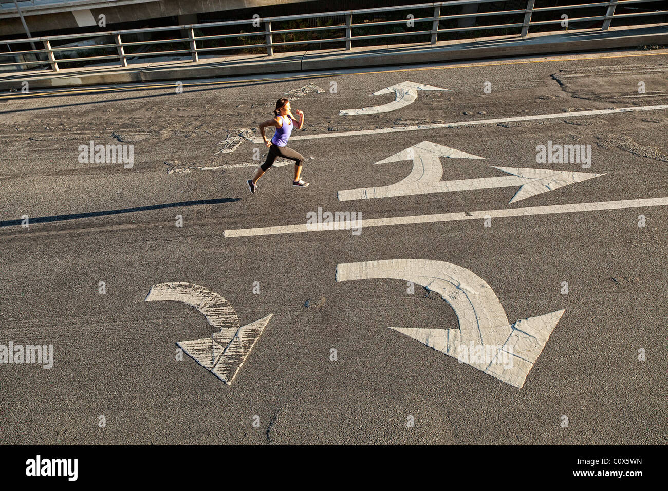 Female runner running on urban city street bridge, overpass with directional arrows painted on pavement - Stock Image