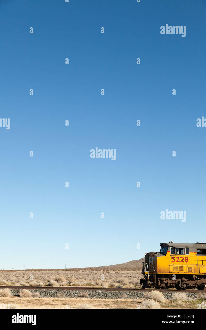 Yellow train locomotive engine on tracks in desert against blue sky. Antelope Valley, California. - Stock Image