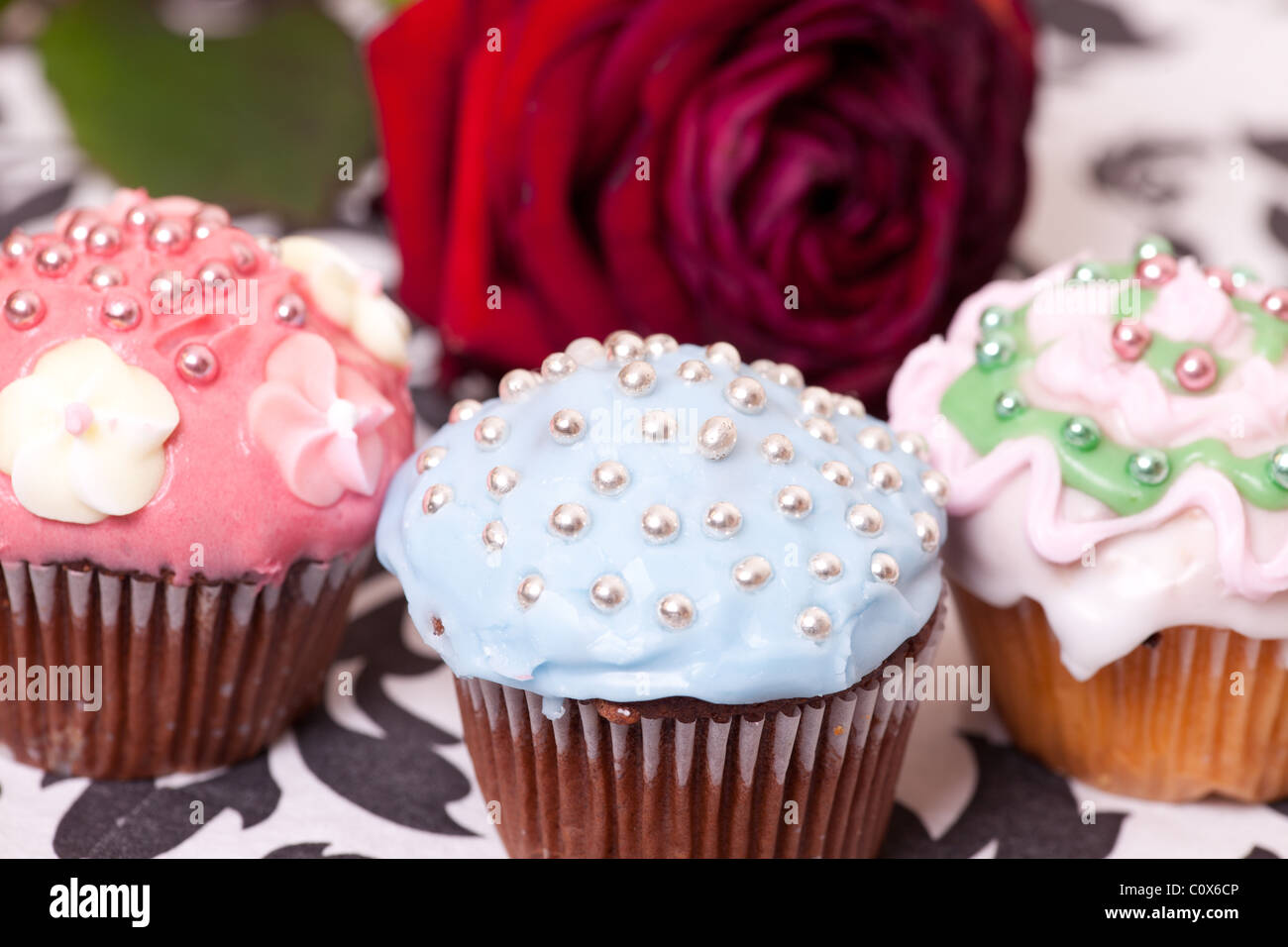 macro picture of multi colored cup cakes on the background with the red rose. - Stock Image