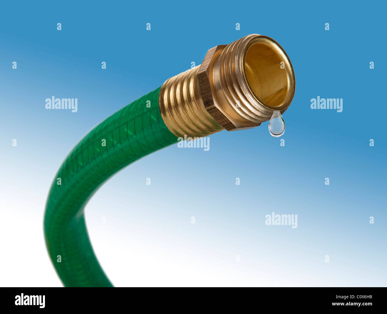 A green garden hose with only one drop of water coming out. - Stock Image