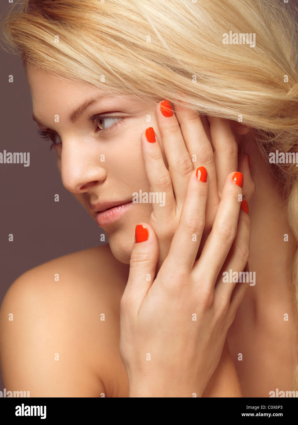 Beauty portrait of a young woman with bright orange nail polish - Stock Image
