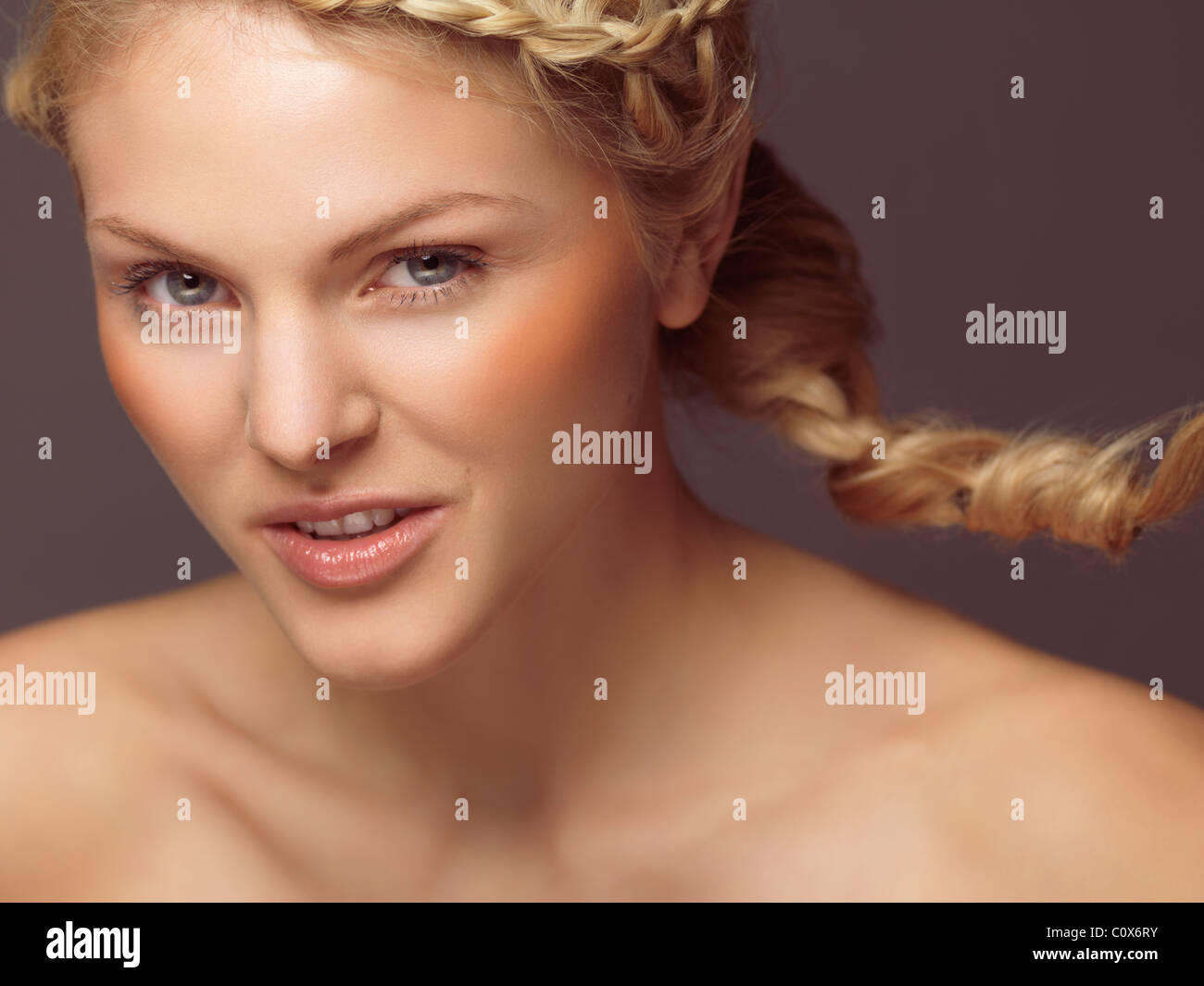 Beauty portrait of a young smiling woman with a braid and orange blush Stock Photo