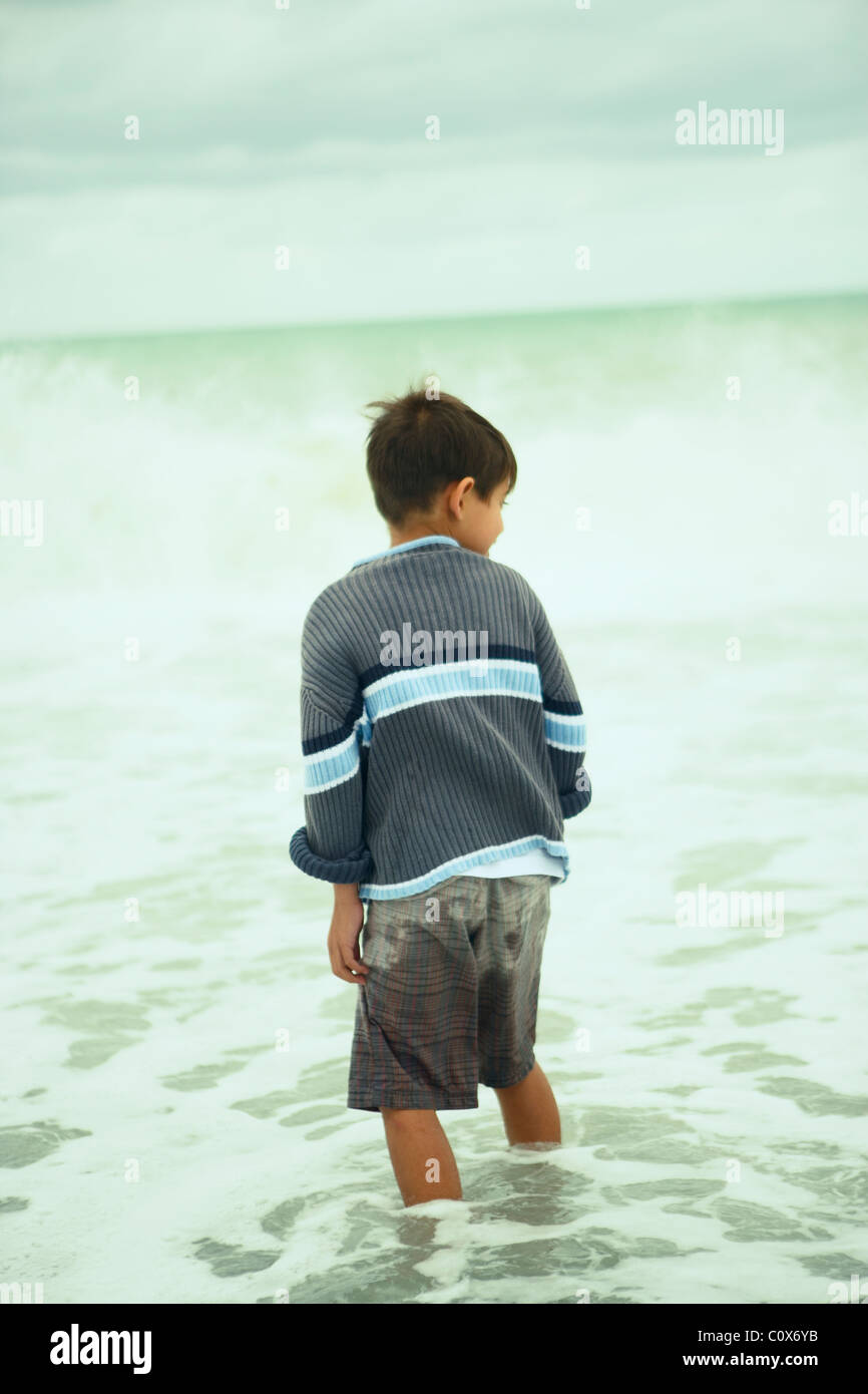 Eight year old boy in the sea on an overcast autumnal day, Napier, New Zealand Stock Photo