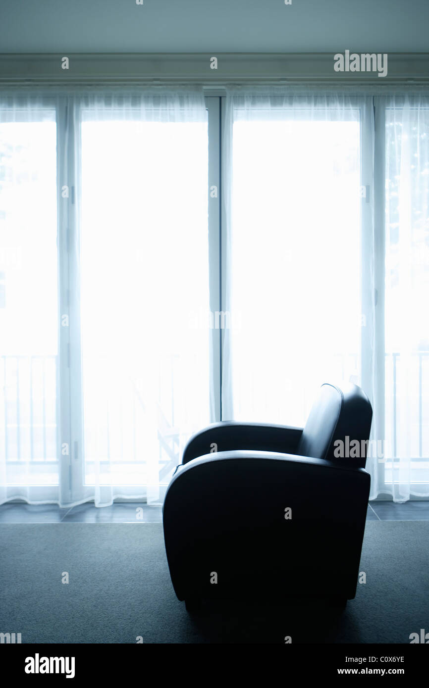Art Deco style armchair beside window - Stock Image