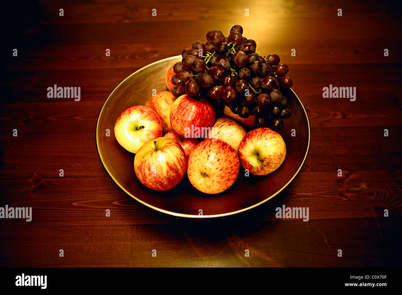 Bowl of apples and grapes on wooden table Stock Photo