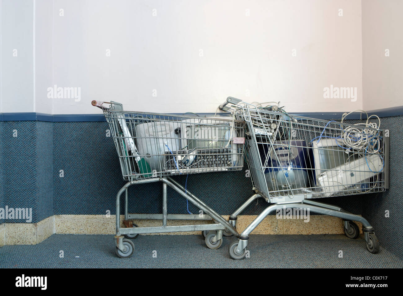 Old computers in shopping trolleys in school corridor. - Stock Image