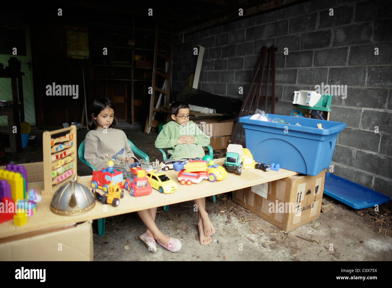 Boy and girl set up garage sale stall to sell their old toys. - Stock Image