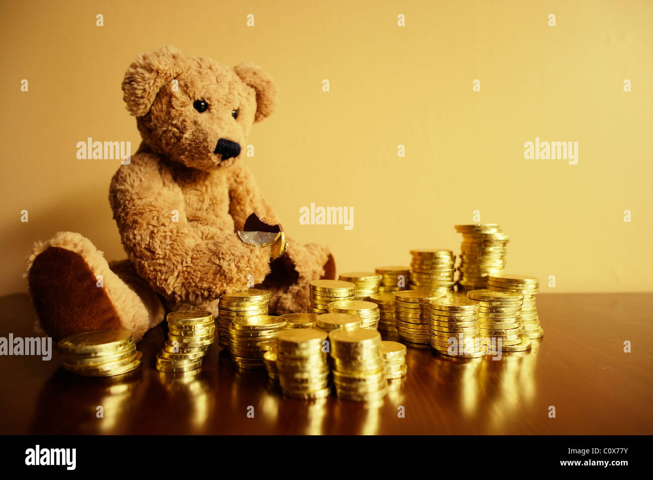 Ted tucks into his chocolate gold coin investment. - Stock Image