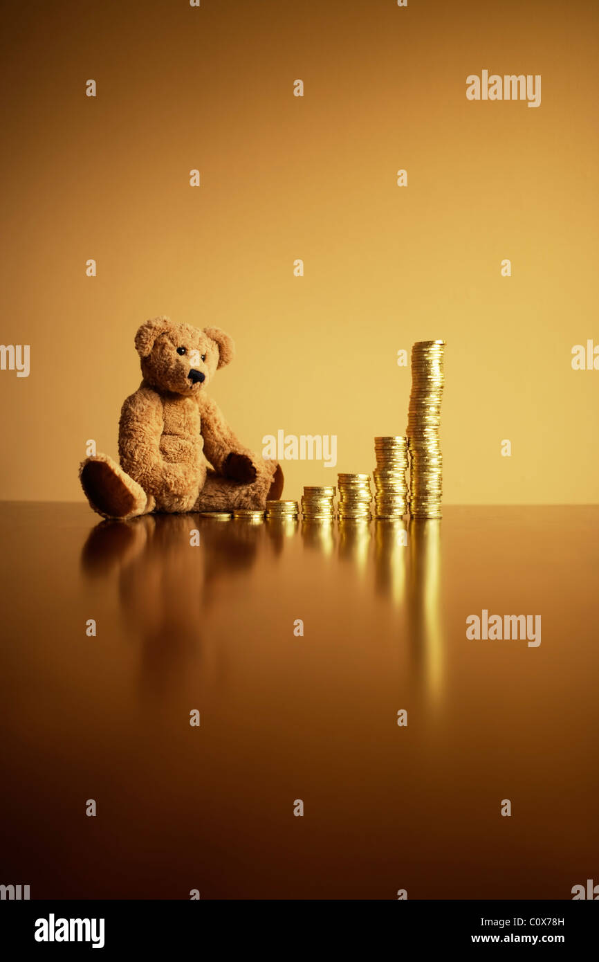 Investment returns: exponential growth. Ted considers future growth with his pile of chocolate gold coins. - Stock Image
