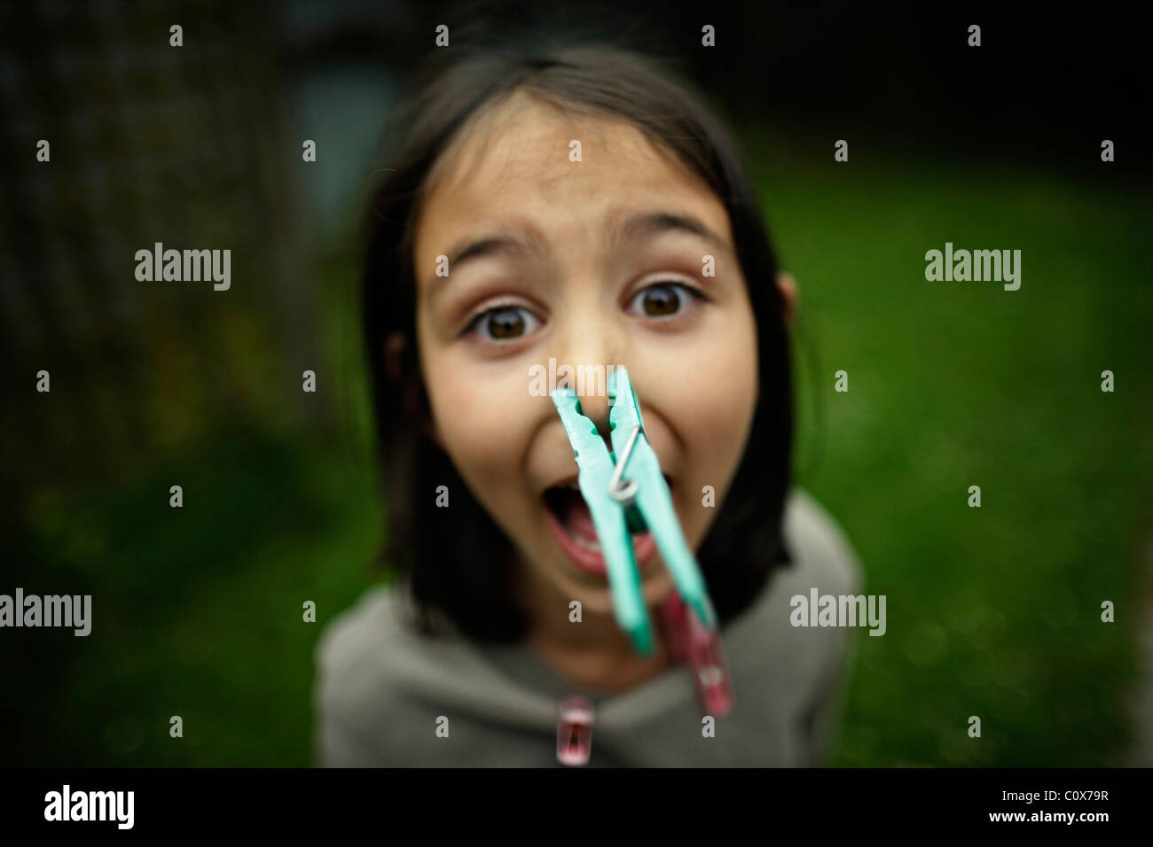 Girl with peg on nose - Stock Image