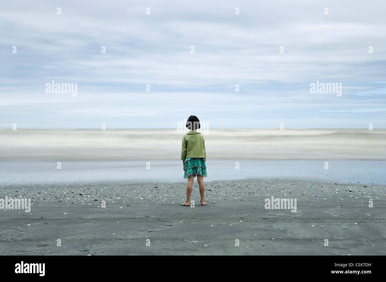 Girl in sharp focus looks at sea, with waves blurred by long exposure; black volcanic sand, Manawatu, New Zealand. Stock Photo