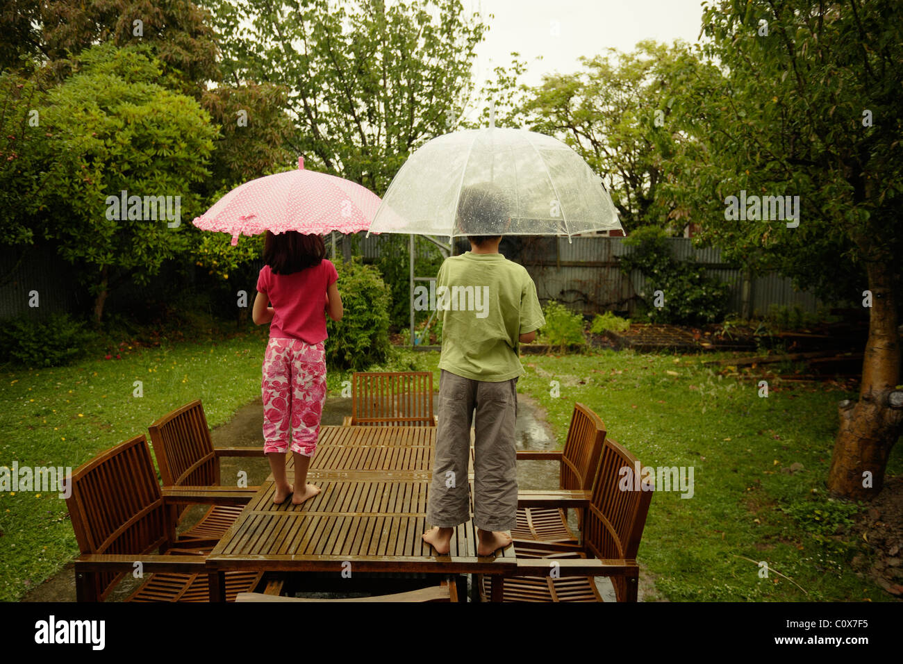 Boy and girl stand on table in garden watching the rain on a weekend. - Stock Image