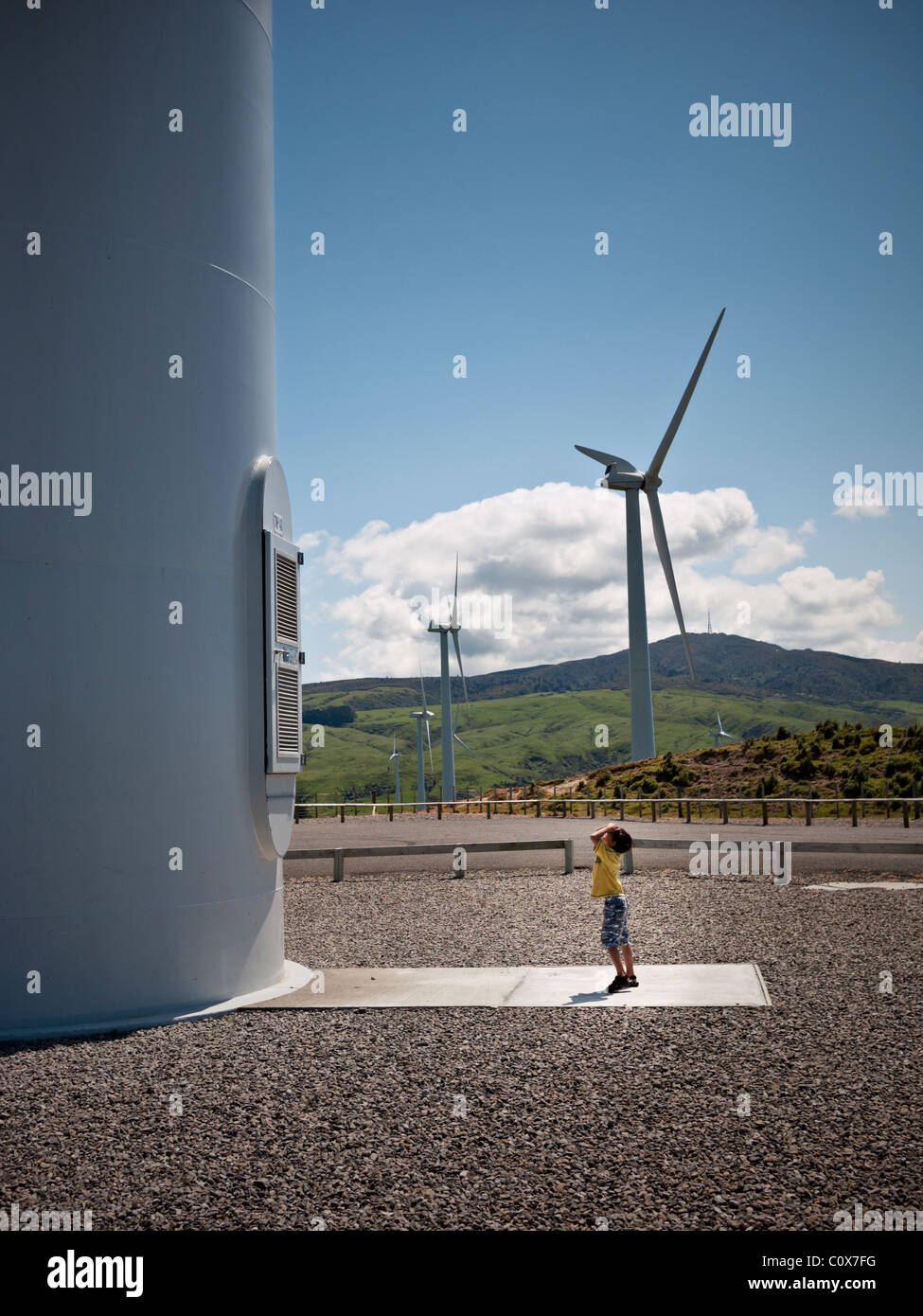 Boy looks up at wind turbine, Te Apiti wind farm, New Zealand. - Stock Image