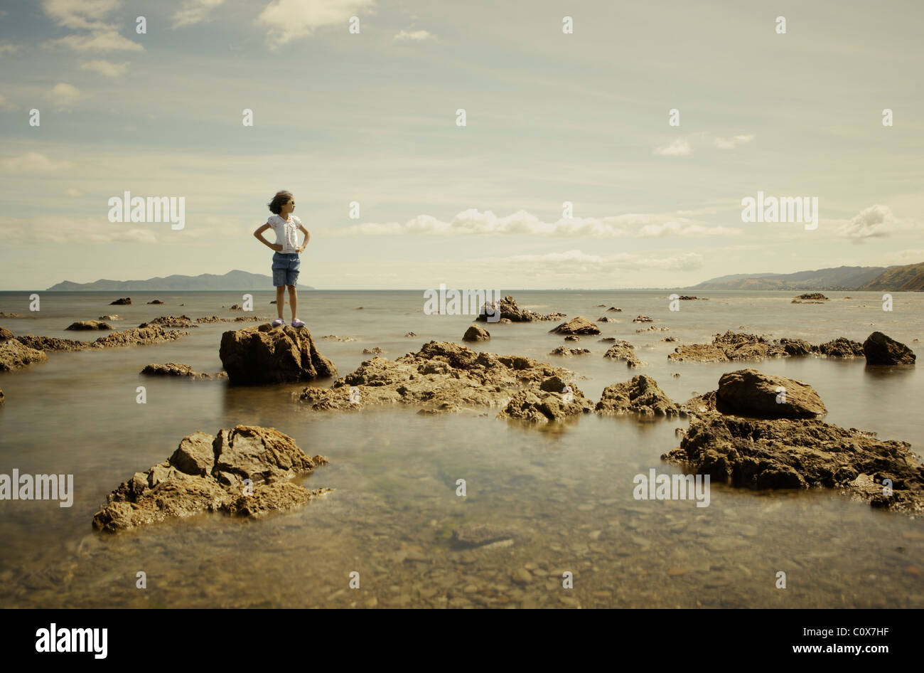 Girl on the rocks. Sea blur from combined exposures. - Stock Image