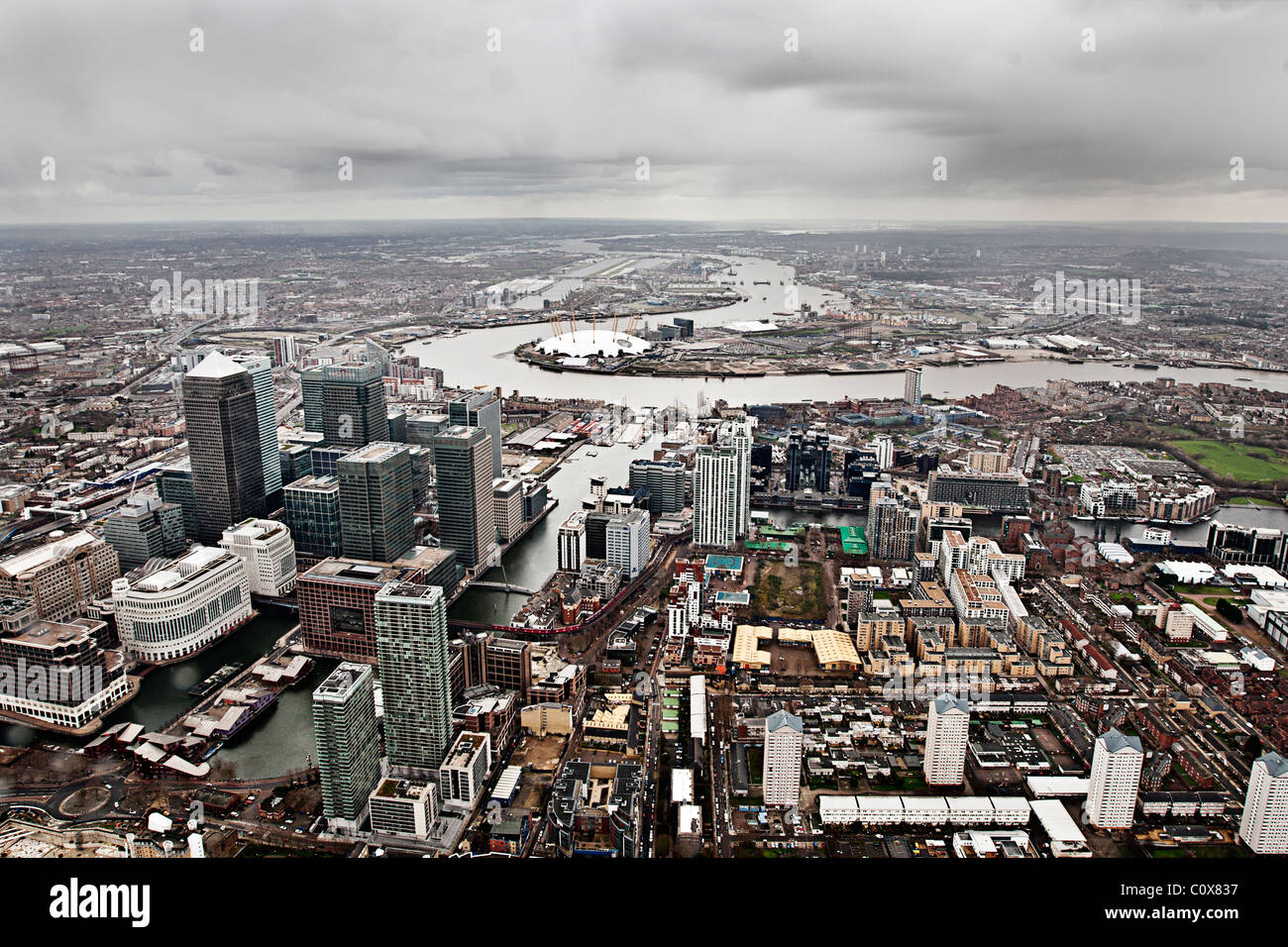 Aerial Shot of the Canary Wharf Estate on a Gloomy Day. Views over to the o2 Arena on the Greenwich Peninsula behind - Stock Image