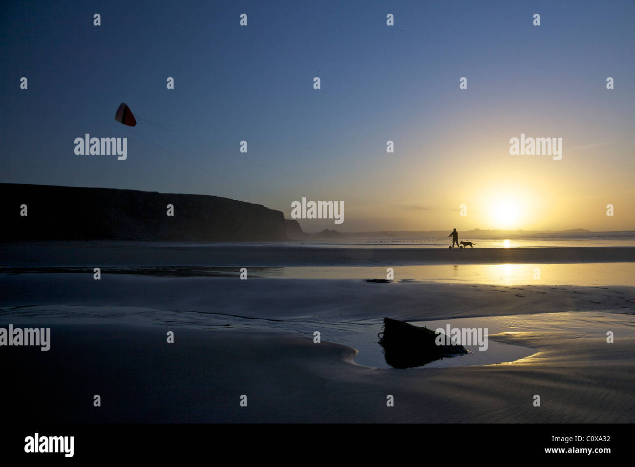 Man on kite landboard with his dog at sunset on the beach at Watergate Bay, Cornwall, South West, England, UK, United - Stock Image