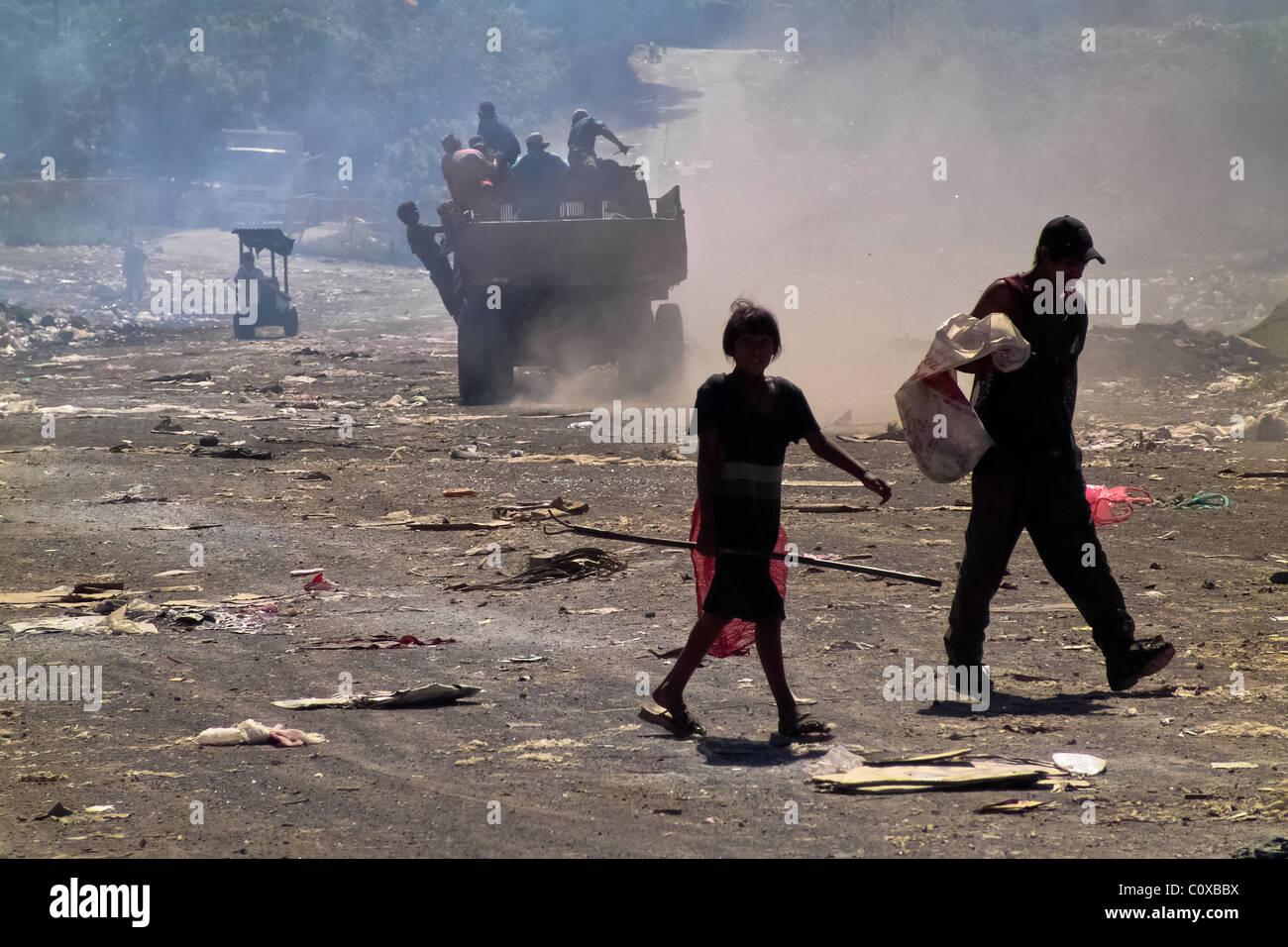 Nicaraguan garbage recollectors, walking in a dust cloud, work in the garbage dump La Chureca, Managua, Nicaragua. - Stock Image